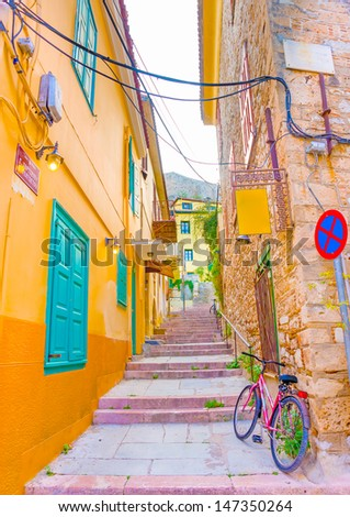 Narrow road with beautiful historic buildings in Nafplio town in Greece - stock photo