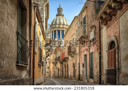 Narrow scenic street in Ragusa, Sicily, Italy with old townhouses and the dome of a church visible at the end, UNESCO World Heritage Site - stock photo