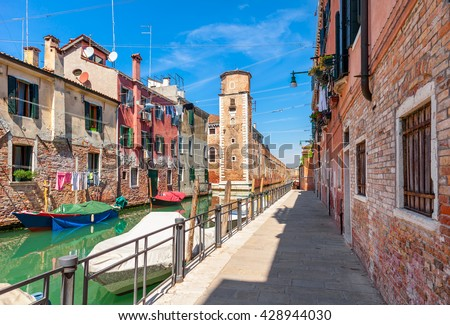 Narrow street and boats on canal between colorful houses under blue sky in Venice, Italy.