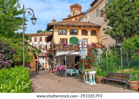 Narrow street and houses with flowers in Barolo - small town in Piedmont, Northern Italy.