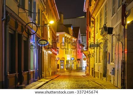 Narrow street illuminated of Old Town at night, Riga, Latvia - stock photo