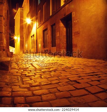 Narrow street in european city at night. - stock photo