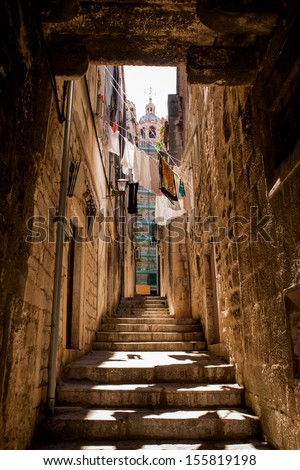 Narrow street in Korcula, Croatia, with St. Mark's Cathedral under reconstruction in the background - stock photo