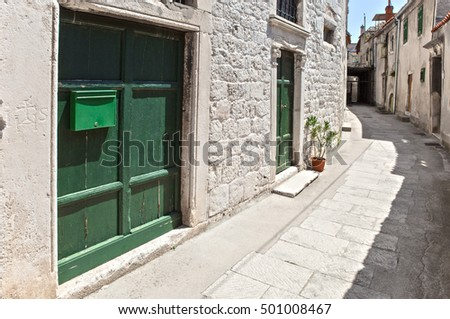 narrow street in old mediterranean town with green doors on white stone worked facade