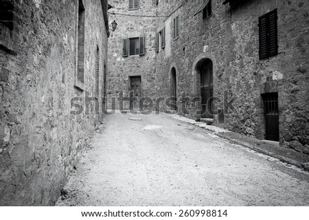 Narrow street in old town of Italy in black and white - stock photo