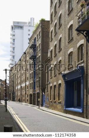 Narrow street known as Shad Thames, between renovated warehouses. Near Tower Bridge. Southwark. London. England - stock photo