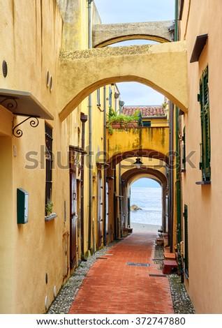 Narrow street leading through an arch to the Mediterranean Sea in traditional old town Varigotti, Finale Ligure, Liguria, Italy - stock photo