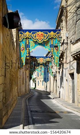 Narrow street on sunny day and feast decoration in Gudja, Malta, Europe. Typical maltese street. Narrow stony street prepared for festival. Malta. Religion feast in Malta  - stock photo