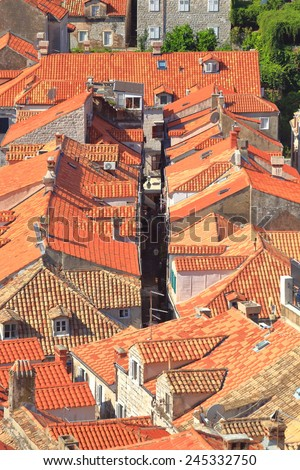 Narrow street sided by orange roof tops in the old town of Dubrovnik, Croatia - stock photo