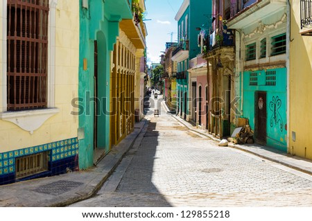 Narrow street sidelined by colorful old buildings in Havana - stock photo
