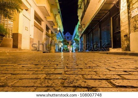 Narrow street sidelined by typical buildings illuminated at night in Old Havana - stock photo