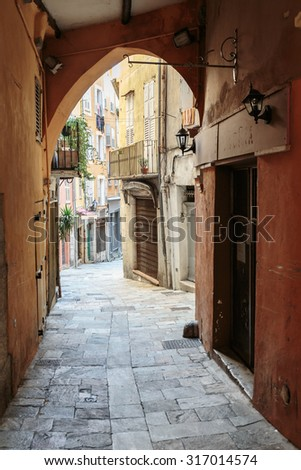 Narrow street with flowers in the old town in France - stock photo