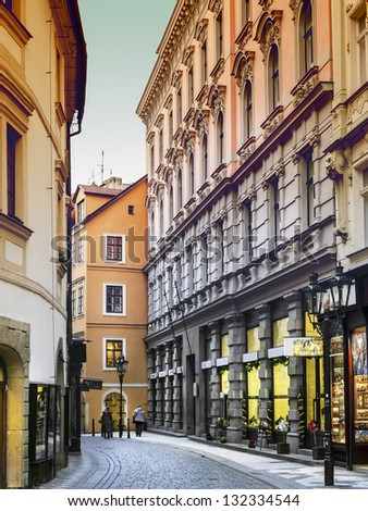 Narrow street with shops in Prague, a street with cobblestones in January in an evening atmosphere. - stock photo