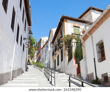Narrow street with traditional houses  in the old part of Spanish City. Granada, Spain. - stock photo