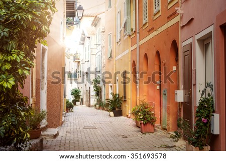 Narrow sunny old street with colorful painted buildings and green potted plants in medieval town Villefranche-sur-Mer on French Riviera, France.