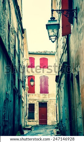 Narrow the street in Arles (Provence, France). Weathered stucco walls, red wooden shutters and forging lanterns. Aged photo. - stock photo