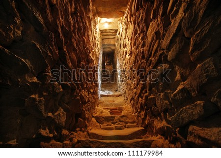 narrow tunnel in the wall of a fortress - stock photo