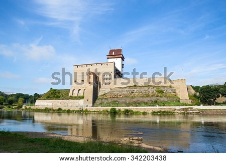 Narva castle on the river bank in summer day - stock photo