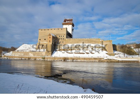 NARVA, ESTONIA - MARCH 02, 2016: Herman's castle on the Narva river cloud March afternoon