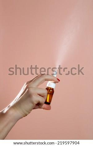 Nasal Spray, Female hand spraying nasal spray over pink background. - stock photo