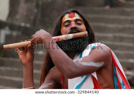 NASHIK - SEP 15:An unidentified Sadhu plays flute as he attends the Maha Kumbh Mela on September 15, 2015 in Nashik, India.Kumbhmela is a Hindu religious event gathered by millions. - stock photo
