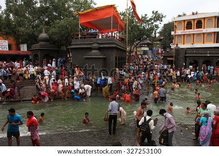 NASHIK - SEP 14:Unidentified devotees take bath in the river Godavari during the event Kumbh Mela on September 14, 2015 in Nashik, India.Kumbhmela is a Hindu religious event gathered by millions. - stock photo