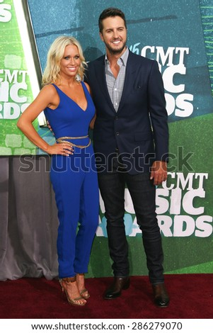 NASHVILLE, TN-JUN 10: Singer Luke Bryan (R) and wife Caroline Boyer attend the 2015 CMT Music Awards at the Bridgestone Arena on June 10, 2015 in Nashville, Tennessee. - stock photo