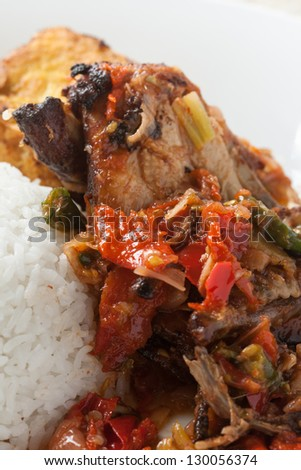 nasi ayam penyet - spicy chicken with chili and tomato, served with rice and fried tofu. local  food of java, indonesia