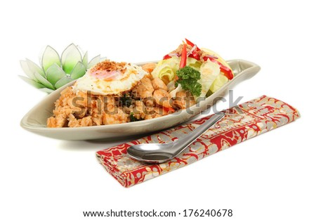 Nasi Goreng, Indonesian fried rice/Nasi Goreng/A photo of Indonesian fried rice also known as Nasi Goreng with Batik napkin and lotus flower on a white background. - stock photo