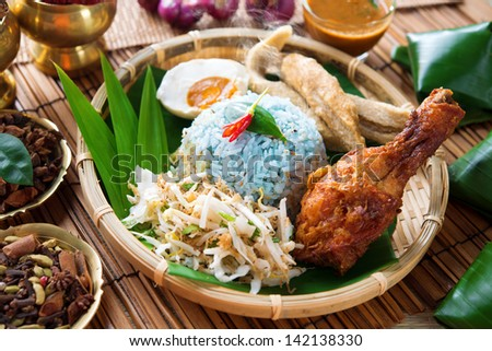 Nasi kerabu or nasi ulam, popular Malay rice dish. Blue color of rice resulting from the petals of  butterfly-pea flowers. Traditional Malaysian food, Asian cuisine. - stock photo