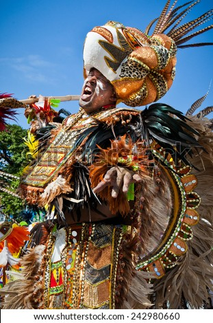 NASSAU, THE BAHAMAS - JANUARY 1 - Sultan clad dancer dressed in bright orange and brown feathers, performs in Junkanoo, a traditional island cultural festival in Nassau, Jan 1, 2011 - stock photo
