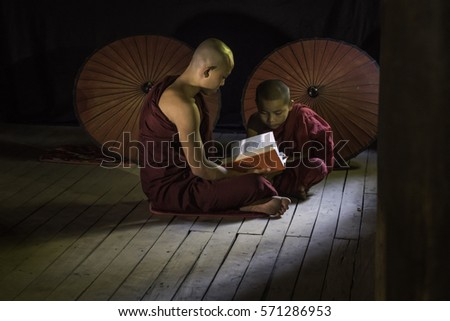 Nat Taung Kyaung Monastery, Bagan, Myanmar - January 20, 2017 : Novice monks studying in front of a window
