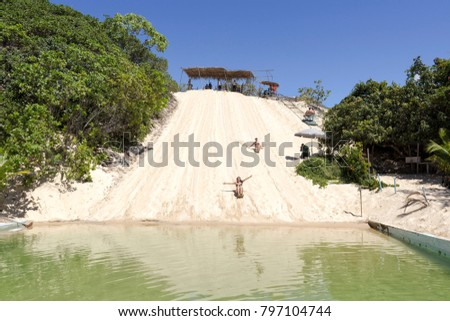 Natal, Rio Grande do Norte, May 17, 2013: Tourists experimenting Sand Board in the dunes of Pitangui, Natal. Sand board practice includes riding down the dune and getting in the lake´s water.