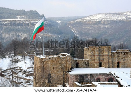 National Bulgarian flag is waving over medieval Tsarevets fortress in the city of Veliko Tarnovo in Bulgaria in the winter - stock photo