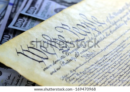 National Debt Ceiling Concept - US Constitution with One Hundred Dollar Bills sitting above - stock photo