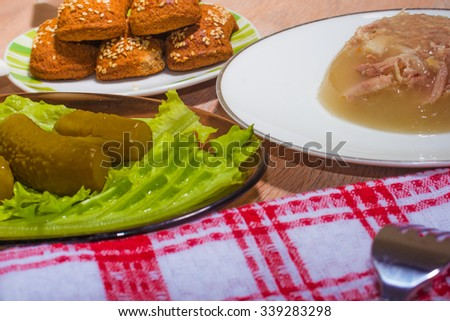 national dish: meat jelly with potatoes and salty cucumbers - stock photo