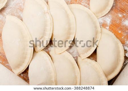 national dish. raw mini Chebureki stuffed with meat on a kitchen board - stock photo