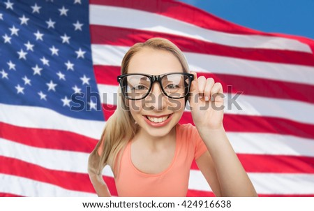 national, education and people concept - happy smiling young woman or teenage girl eyeglasses over american flag background