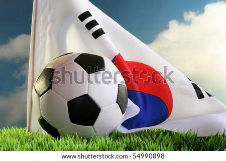 National flag and a football against a cloudy sky - stock photo