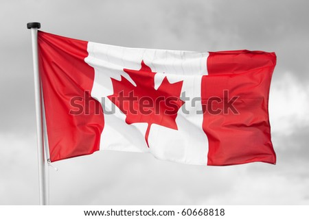 national flag of canada on a black & white cloudy sky background - stock photo