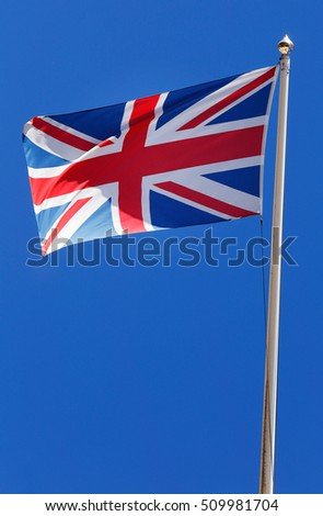National flag of Great Britain flies against a blue sky.