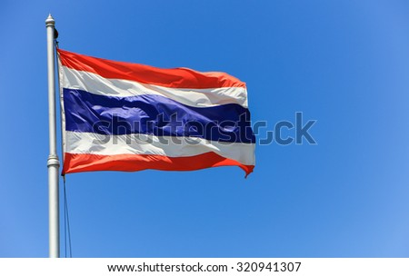 National flag of Thailand with blue sky background.
