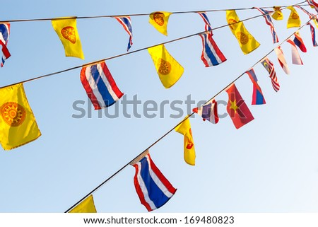 National flags and Wheel of Dhamma 's flags on string and blue sky at Chiangrai ,Thailand