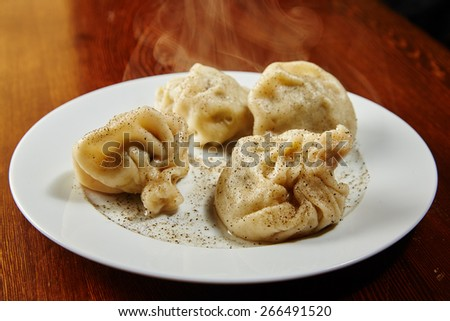National Georgian dish khinkali meat in a sacred test a couple of little lamb or beef, meat wrapped in a bag of dough, sprinkle with black pepper, freshly prepared, steams, smells of fresh food - stock photo