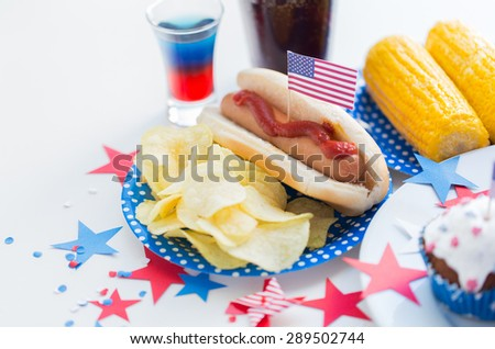 national holidays, celebration, food and patriotism concept - close up of hot dog with american flag decoration, potato chips and drinks on 4th july at party on independence day - stock photo