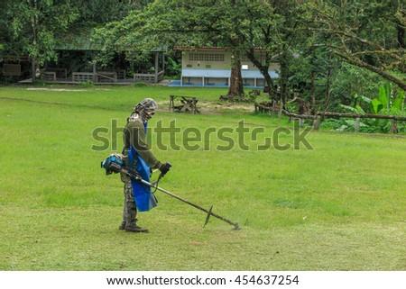 National park gardener cutting grass with lawnmower at Chong Yen, Mae Wong national park, Thailand - stock photo