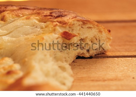National Uzbek bread bitten on a wooden background, close-up. - stock photo