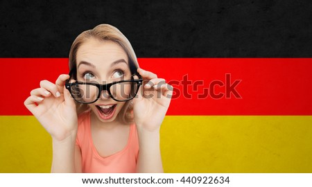national, vision, education and people concept - happy smiling young woman or teenage girl eyeglasses over german flag background