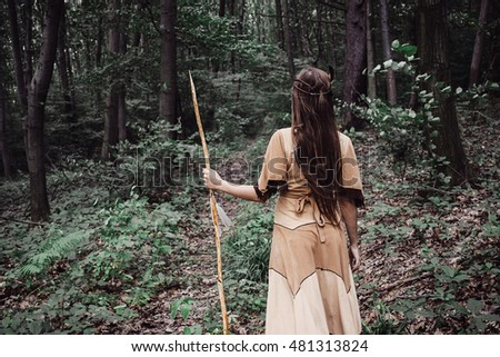 Native american indian beautiful woman warrior posing with spear in field
