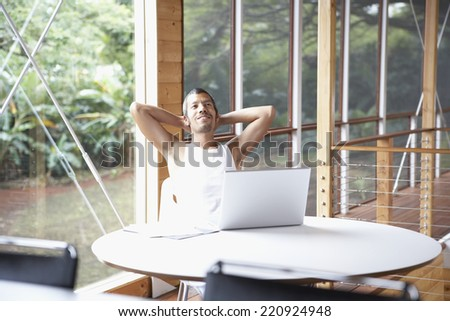 Native American man with arms behind head - stock photo